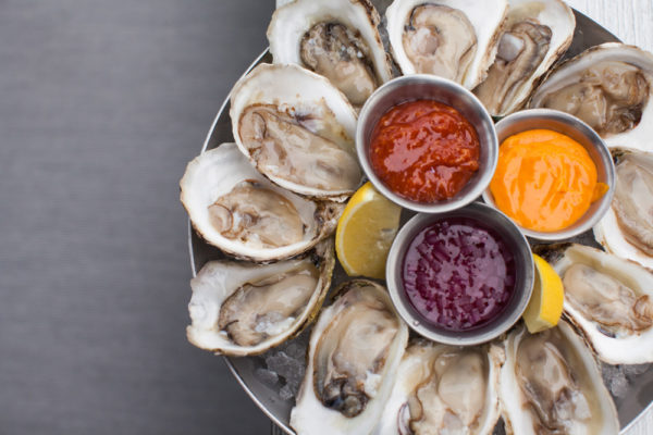 a plate of oysters and dips