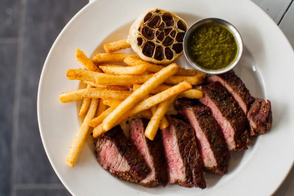A plate of sliced steak with french fries and dips