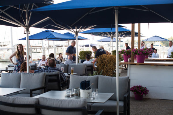 The patio outside at Bronte Boathouse with comfy chairs, tables, and patio umbrellas.
